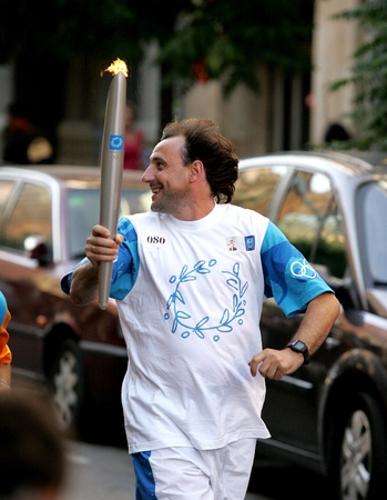 Spanish athlete Fermin Cacho carries the Athens 2004 Olympic torch during the Barcelona Torch Route through the city streets, June 28, 2004 in Barcelona, Spain