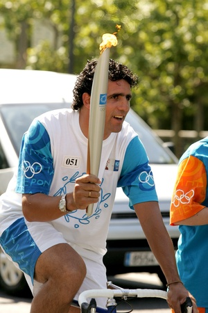 Spanish cyclist Miguel Indurain carries the Athens 2004 Olympic torch during the Barcelona Torch Route through the city streets, June 28, 2004 in Barcelona, Spain