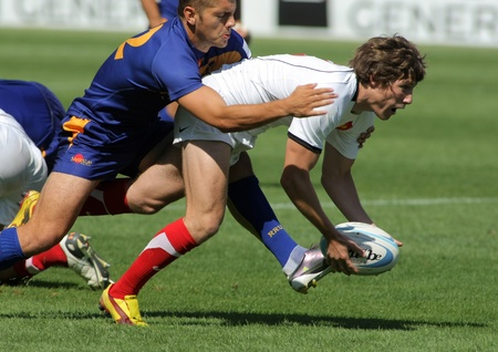 european championship: Quentin Moulinjeune of France is tackled by Romanian player during the match of Rugby7 European Championship between France and Romania at the Olympic Stadium in Barcelona, on July 9, 2011