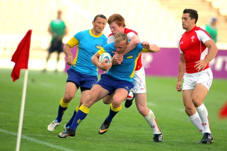 Pavlo Masiukov of Ukraine is tackled by Welsh players during the match of Rugby7 European Championship between Ukraine and Wales at the Olympic Stadium in Barcelona, on July 9, 2011