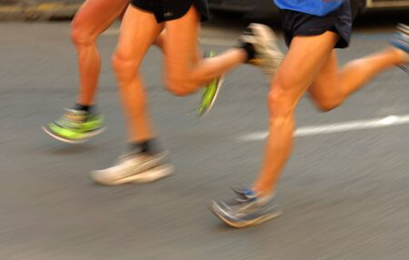 persecution: Marathon runners group legs on the road by another runner with panning blur