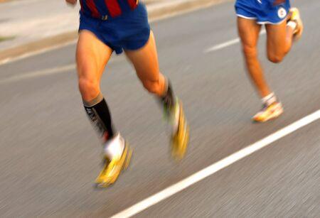 follow the leader: Marathonloper benen op de weg, gevolgd door een andere loper met panning onscherpte Stockfoto
