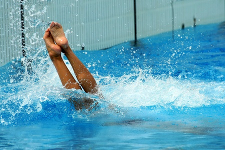 plunge: Woman jumping getting into water in diving action Stock Photo