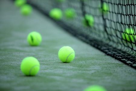 pasto sintetico: Pelotas de tenis o paddle en el césped sintético de la pista de pádel con una ganancia neta en el fondo