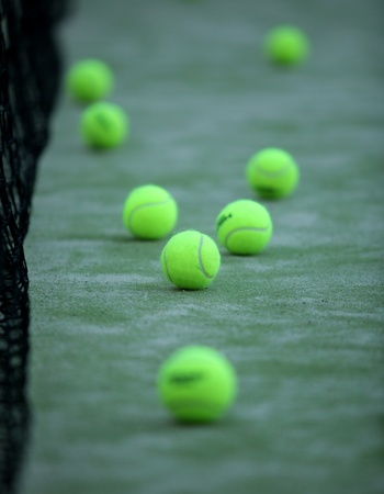 pasto sintetico: Pelotas de tenis o paddle sobre c�sped sint�tico de p�del con neto sobre el fondo Foto de archivo