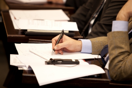 translation: Executive writing on paper during a conference with translation Stock Photo