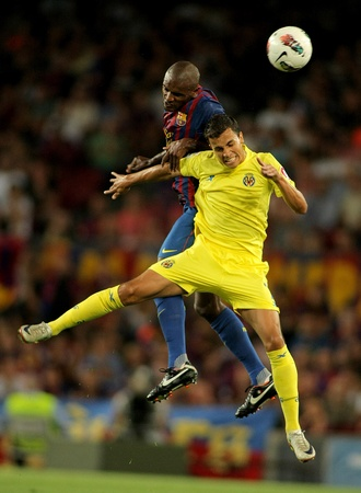 Abidal(L) vies with Nilmar(R) during a Spanish League match between FC Barcelona vs CF Villarreal at the Nou Camp Stadium on August 29, 2011 in Barcelona, Spain