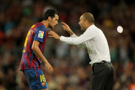 champion of spain: Guardiola trainer of FC Barcelona gives orders to Sergio Busquets during a Spanish League match against CF Villarreal at the Nou Camp Stadium on August 29, 2011 in Barcelona, Spain
