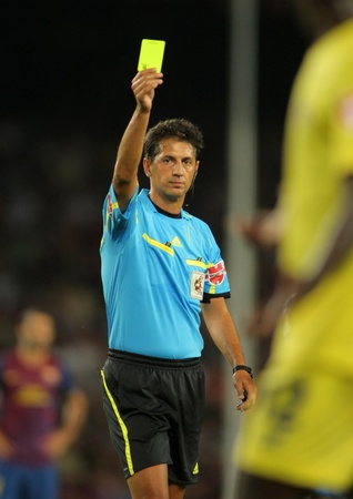 delivers: Referee Turienzo Alvarez delivers yellow card during a Spanish League match between FC Barcelona vs CF Villarreal at the Nou Camp Stadium on August 29, 2011 in Barcelona, Spain Editorial