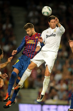 Gerard Pique(L) of FC Barcelona vies with Sergio Ramos(R) of Real Madrid during the Spanish Supercup football match at the New Camp Stadium in Barcelona, on August 17, 2011