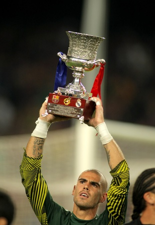 barsa: Victor Valdes of FC Barcelona holds Supercup trophy after the Spanish Supercup football match at the New Camp Stadium in Barcelona, on August 17, 2011