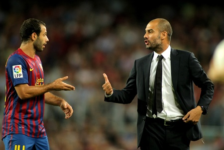 champion of spain: Guardiola trainer of FC Barcelona gives orders to Javier Mascherano during the spanish league match against Osasuna at the Nou Camp Stadium on September 17, 2011 in Barcelona, Spain