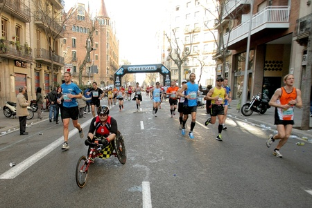 Athlete with mobility disabilities running in Barcelona street crowded of athletes during Barcelona Marathon in Barcelona March 3, 2011 in Barcelona, Spain