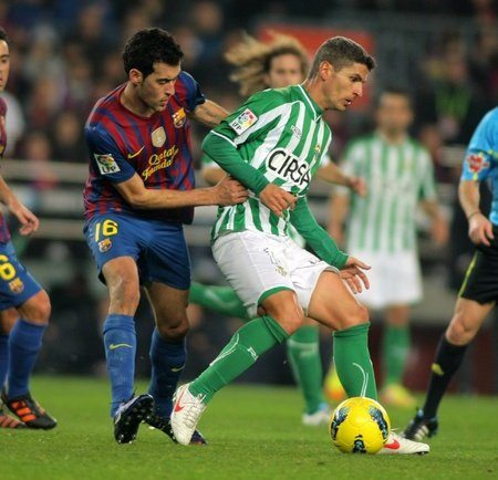sergio: Salva Sevilla(R) of Real Betis vies with Sergio Busquets(L) of FC Barcelona during the Spanish league match at the Camp Nou stadium on January 15, 2012 in Barcelona, Spain