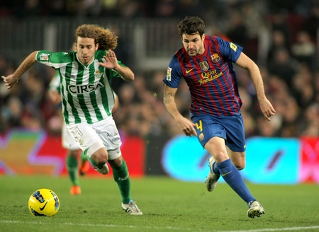 Jose Ca�as(L) of Real Betis vies with Cesc Fabregas(R) of FC Barcelona during the Spanish league match at the Camp Nou stadium on January 15, 2012 in Barcelona, Spain