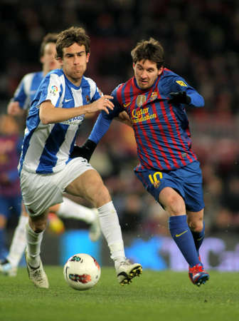 Mikel Gonzalez(L) of Real Sociedad vies with Leo Messi(R) of FC Barcelona during the Spanish league match at the Camp Nou stadium on February 4, 2012 in Barcelona, Spain