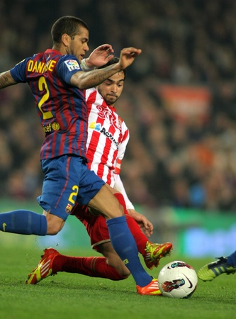 dani: Dani Alves(L) of FC Barcelona vies with Nacho Cases(R) of Sporting de Gijon in action  during the Spanish league match at the Camp Nou stadium on March 3, 2012 in Barcelona, Spain Editorial