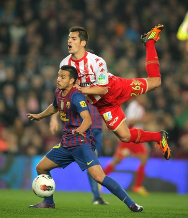 winger: Pedro Rodriguez(L) of FC Barcelona vies with Pedro Orfila(R) of Sporting de Gijon during the Spanish league match at the Camp Nou stadium on March 3, 2012 in Barcelona, Spain