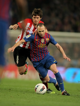 Ander Iturraspe(L) of Athletic Bilbao vies with Andres Iniesta(R) of Barcelona during the Spanish league match at the Camp Nou stadium on March 31, 2012 in Barcelona, Spain