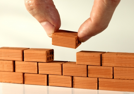 Two fingers put the last brick on the wall Standard-Bild