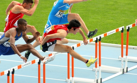 Shunya Takayama(R) of Japan during 110m men hurdles event of the 20th World Junior Athletics Championships at the Olympic Stadium on July 10, 2012 in Barcelona, Spain