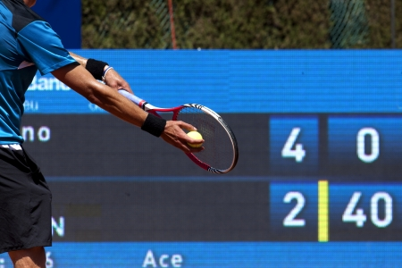 game equipment: A tennis player prepares to serve a tennis ball during a match Stock Photo