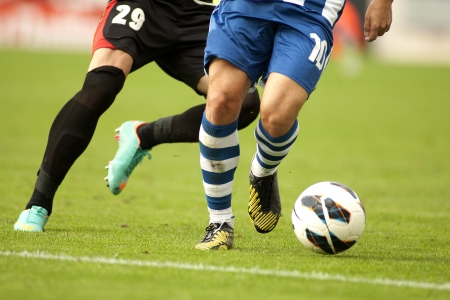 Soccer player legs protecting a ball in a match