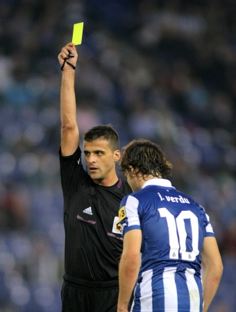delivers: Referee Jesus Gil Manzano delivers yellow card during a Spanish League match between Espanyol and Osasuna  at the Estadi Cornella on November 10, 2012 in Barcelona, Spain