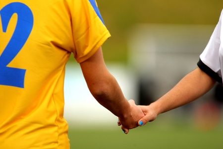 sportwoman: Two athletes handshake after the soccer mach