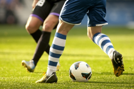soccer ball on grass: Legs of two soccer players vie on a match Stock Photo