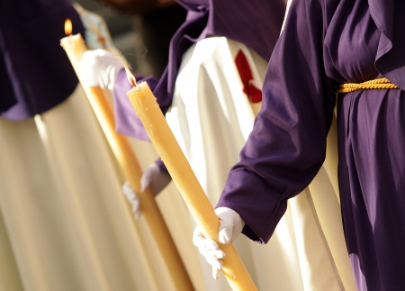procession: Nazarene holding candle during a Holy Week parade  Stock Photo