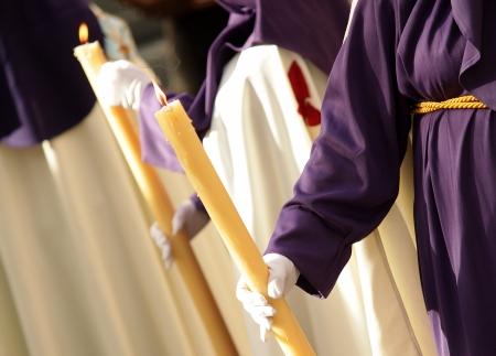 worshipper: Nazarene holding candle during a Holy Week parade  Stock Photo