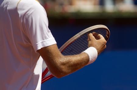 A tennis player checks racquet for serve a tennis ball during a match photo