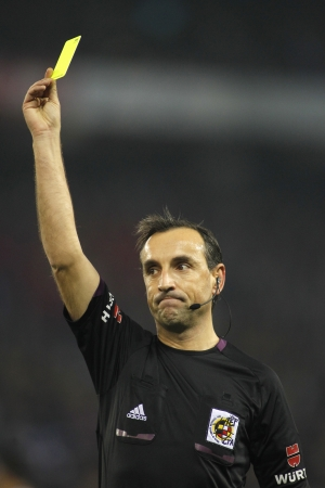 delivers: Referee Teixeira Vitienes delivers yellow card during Spanish soccer league match between Espanyol and Real Madrid at the Estadi Cornella on January 12, 2014 in Barcelona, Spain