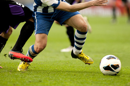 soccer kick: Legs of two soccer players vie on a match Stock Photo