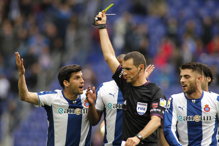 Referee Clos Gomez delivers yellow card to RCD Espanyol players during a Spanish League match against FC Barcelona at the Estadi Cornella on March 29, 2014 in Barcelona, Spain