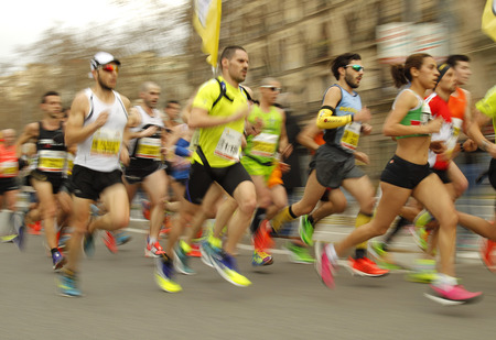 mid distance: Group of runners in Barcelona streets running during Barcelona Half Marathon in Barcelona on February 15, 2015 in Barcelona, Spain.