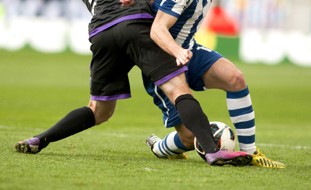 Legs of two soccer players vie on a match Stockfoto