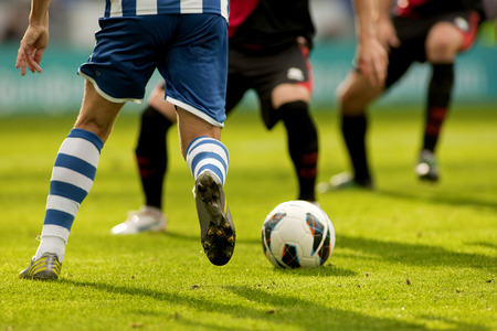 Legs of two soccer players vie on a match Stock Photo