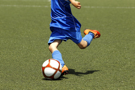 football play: Little boy shooting a ball during a soccer match