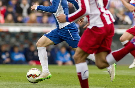 pursued: Football player is pursued by his rivals in a match Stock Photo