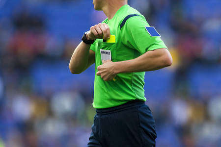 declaring: Soccer referee to point out a yellow card to a player during a match Stock Photo
