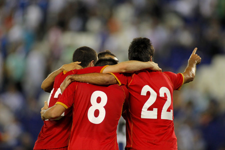 football match: Football players hugging while celebrate goal in a match Stock Photo
