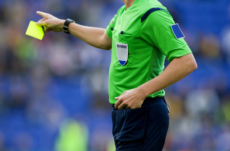 Soccer referee to point out a yellow card to a player during a match Stock Photo