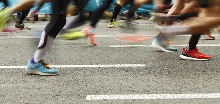 Biegacze nogi na drodze w motion blur podczas imprezy bieg długodystansowy