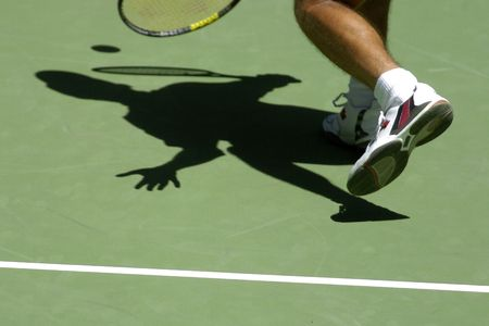 Shadow of a tennis player hitting the ball on the court. photo