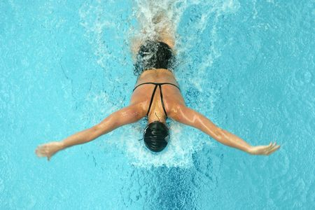 swim race: Woman swimming butterfly shot from above.
