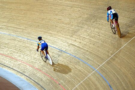 Two cyclists race around a Velodrome.