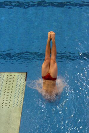 enters: A male diver enters the pool with a splash.