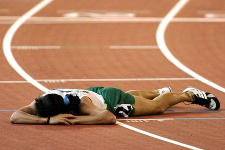 defeat: A runner is beaten and lays on the track tired and sad with defeat.